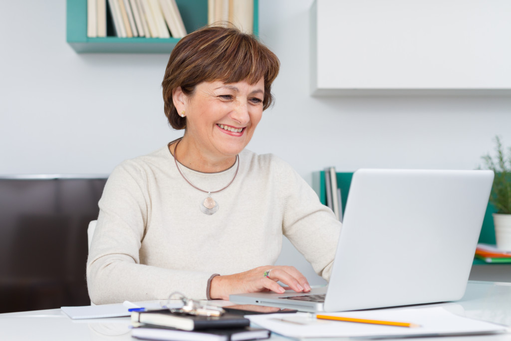 Woman laughing and smiling with computer