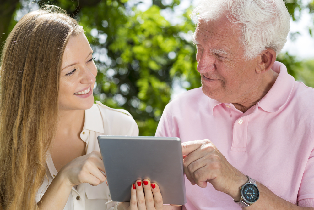 young carer showing senior man how to use tablet in park