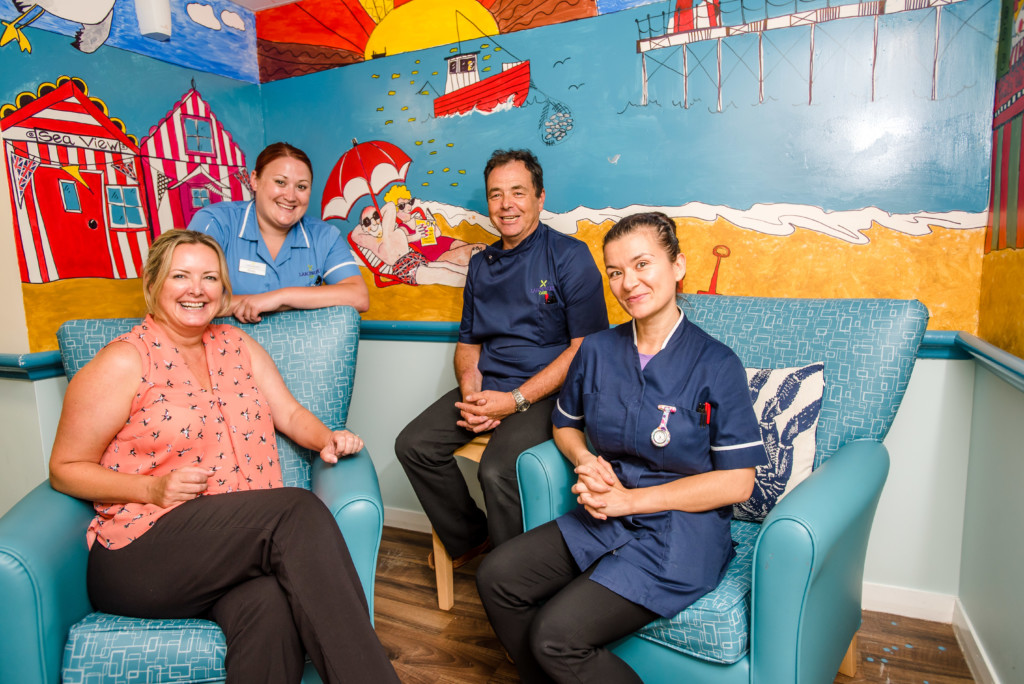 From left - Manager Katrina Bell, Senior Healthcare Assistant Emma Warren, Unit Manager RMN Paul Skaif and Nurse Raluca Mortaga by the newly painted mural at Sherford Manor.