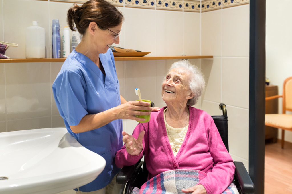 Home Caregiver with senior woman in bathroom